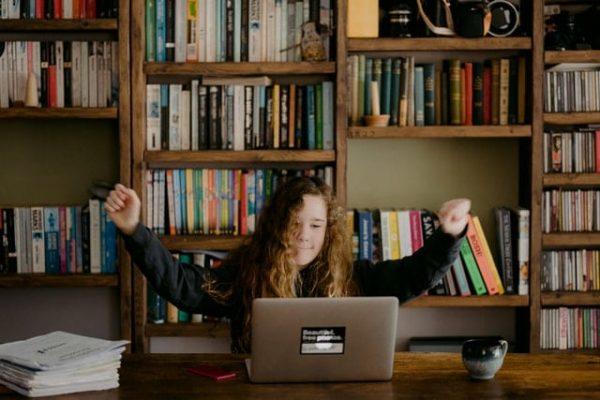 Een meisje van rond de 12 jaar oud steekt vastberaden haar armen in de lucht terwijl ze achter een laptop werkt