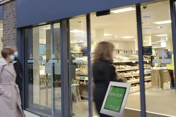 Bezoekers lopen een winkel binnen terwijl een digitale bezoekersteller met stoplichtfunctie via het scherm bij de ingang laat zien dat het maximale bezoekersaantal (in het kader van corona) nog niet is bereikt