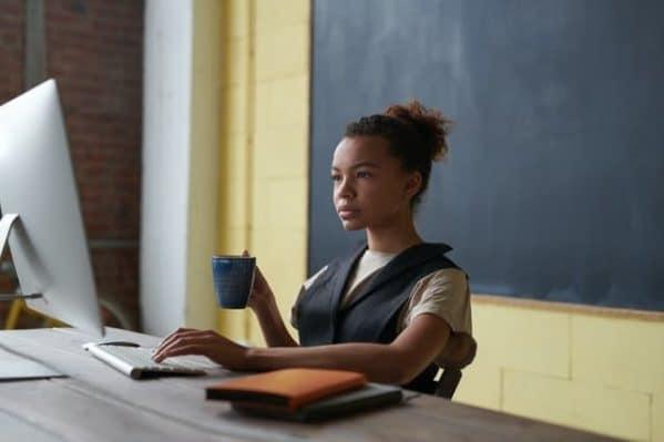 Een jonge vrouw werkt op een computer aan een bureau dat vlakbij het schoolbord staat in een leslokaal
