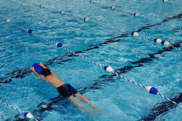 Een zwemmer trekt baantjes in een zwembad