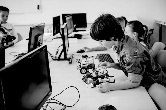 Een jongen van rond de 8 jaar programmeert een robot in een computerzaal