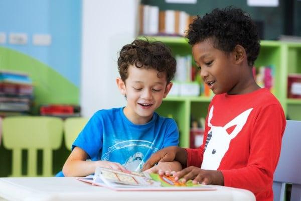 2 basisschoolkinderen bladeren samen door een boek