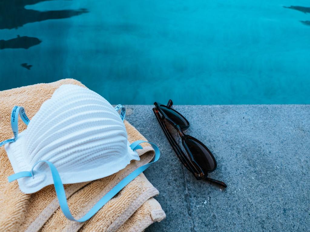 mondkapje, handdoek en zonnebril op zwembadrand