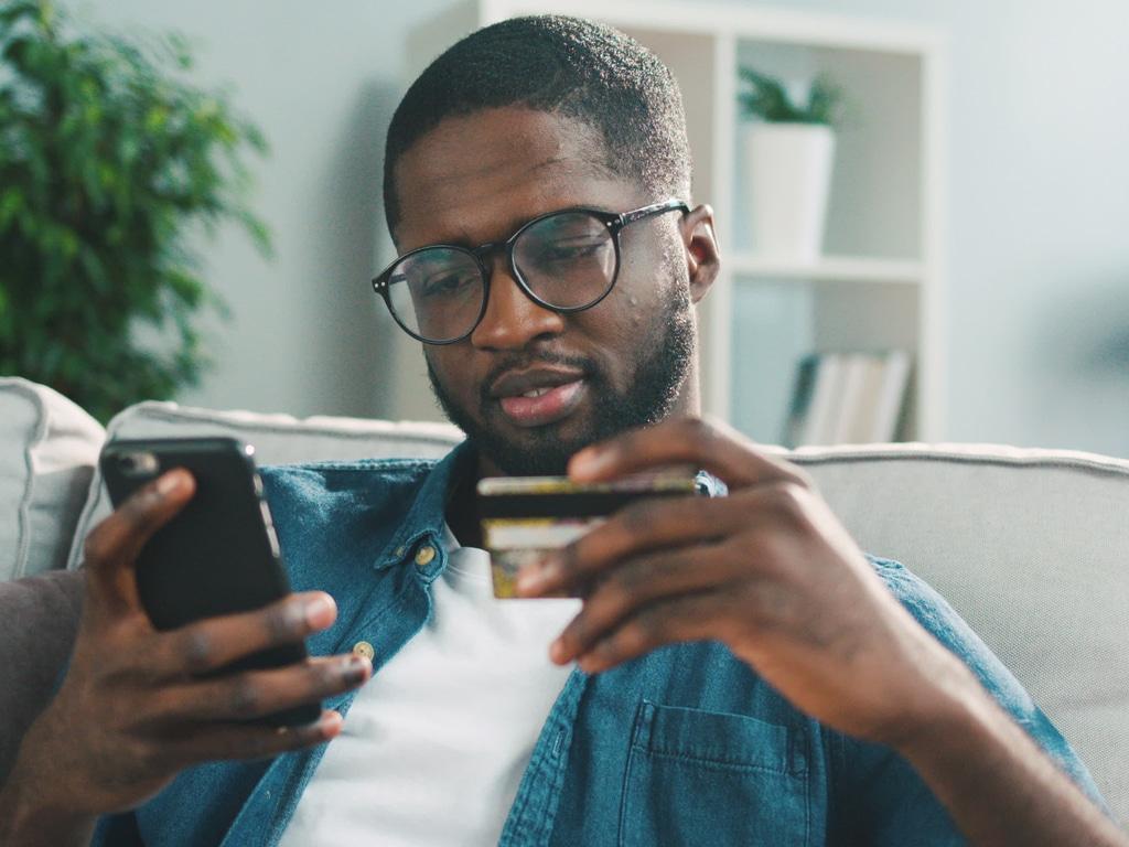 Man betaald ticket met telefoon in de hand